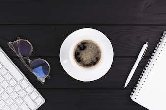 Pen near notebook, cup on saucer, eyeglasses and keyboard