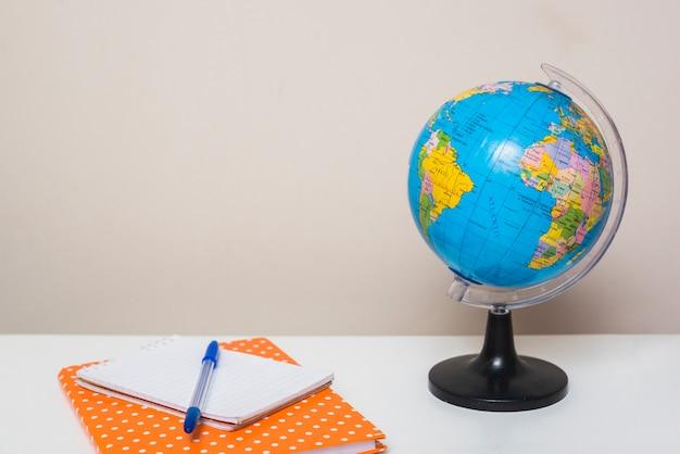 Ручка рядом с ноутбуками и земным шаром