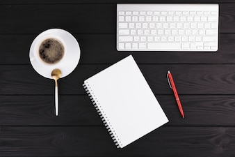 Pen near notepad, cup on saucer, spoon and keyboard