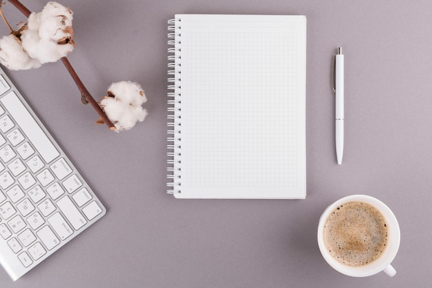 Pen near notepad, keyboard, twig and cup