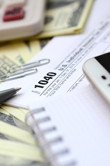 The pen, notebook, calculator, smartphone and dollar bills is lies on the tax form 1040