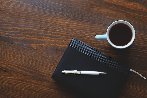Pen, notebook or diary, a mug of tea or coffee on a wooden table.