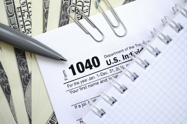 The pen, notebook and dollar bills is lies on the tax form 1040 u.s. individual income tax return. the time to pay taxes