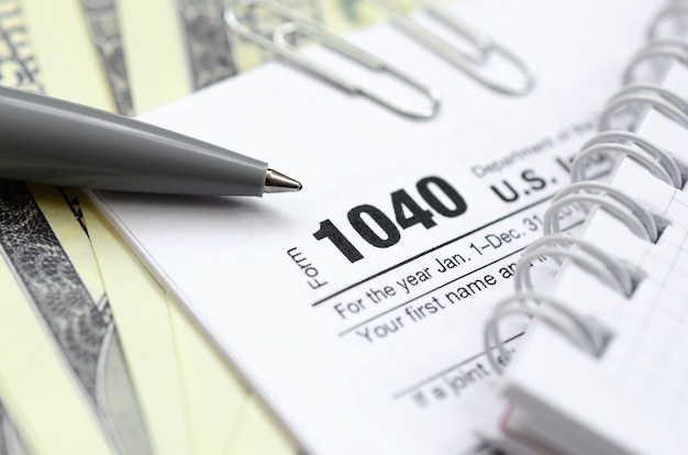 The pen, notebook and dollar bills is lies on the tax form 1040 u.s. individual income tax return.