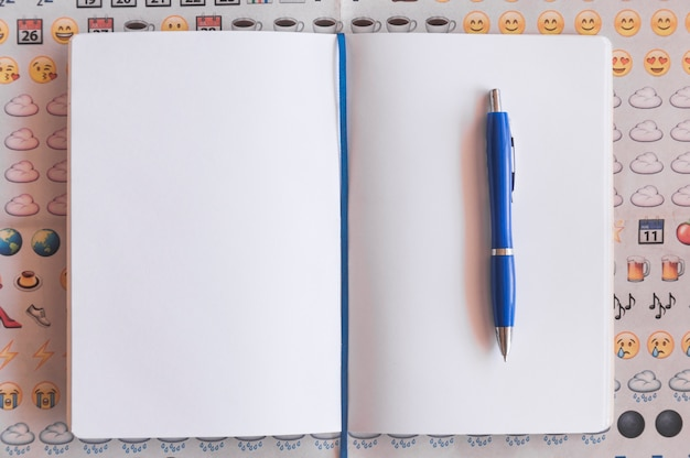 Pen and notebook on emoji background