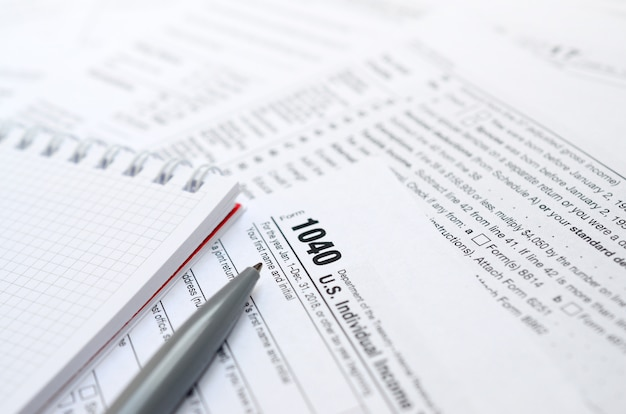 The pen and notebook is lies on the tax form 1040 u.s. individual income tax return.