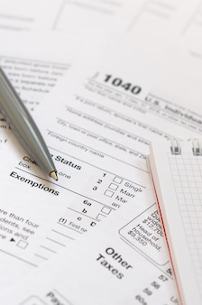 The pen and notebook is lies on the tax form u.s. individual