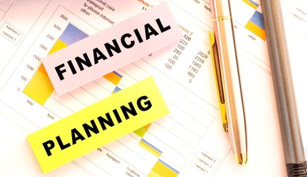 ペン、ノート、ステッカーはデスクトップにあります。上からの眺め。財務コンセプト。