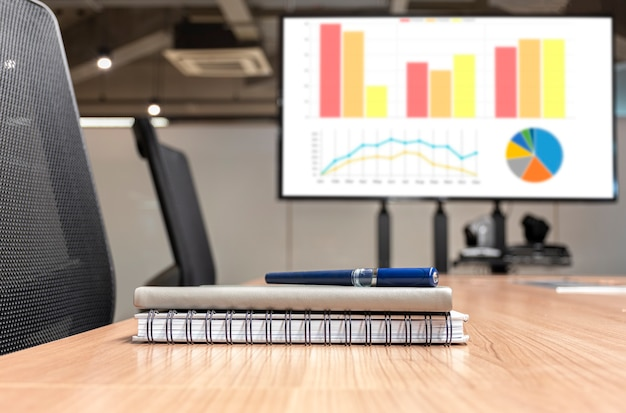 Pen and notebook on table with mock up chart presentation television background in meeting room