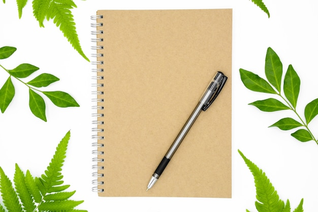Pen on a notebook with green leaves