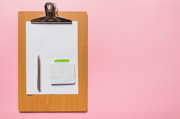 Pen and notepad on blank paper over wooden clipboard against pink background