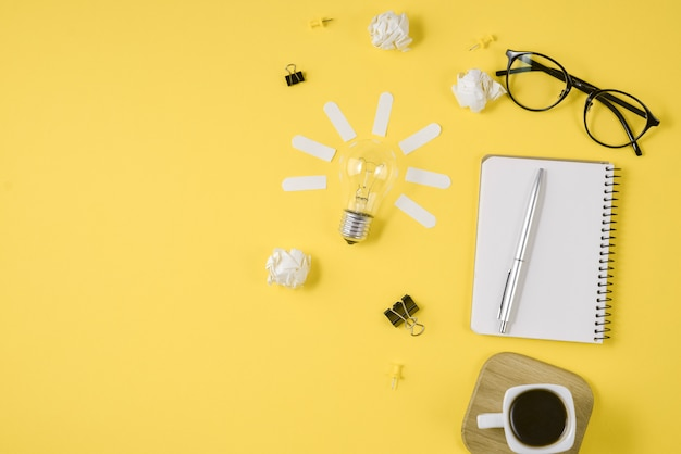 Pen, notepad, eyeglasses, coffee cup and light bulb on yellow background.