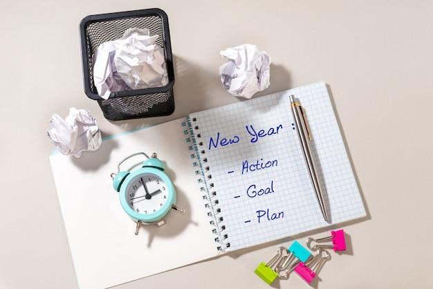 ペン、新年、アクション、目標、計画、明るい背景の青い目覚まし時計とメモ帳