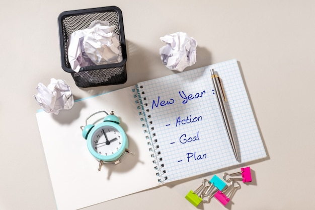 Pen, notepad with new year, action, goal, plan and blue alarm clock on light background
