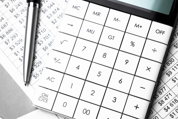 Pen, numbers chart and white calculator