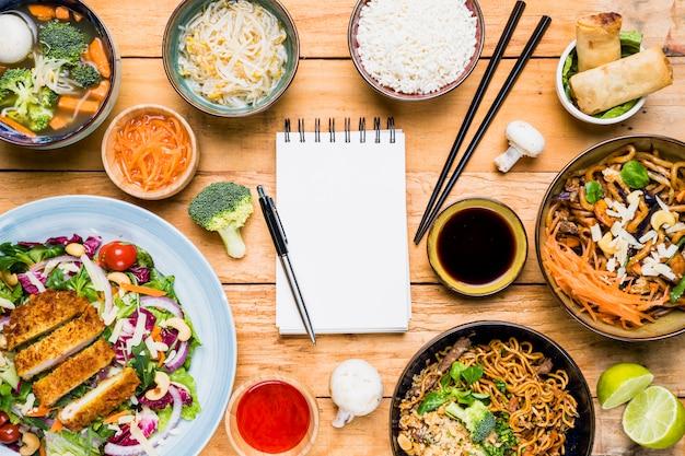 木製のテーブルの上のタイの伝統的な食べ物に囲まれた空白のスパイラルメモ帳のペン