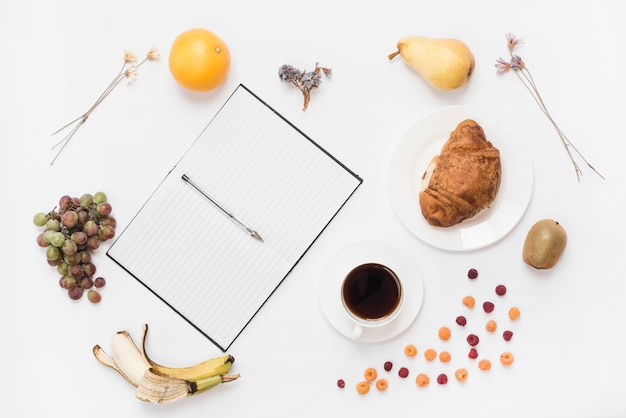Pen on an open notebook with coffee cup; croissant and many fruits on white backdrop
