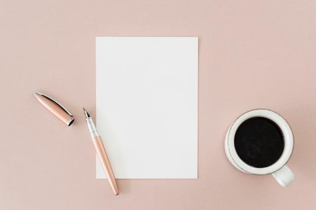 テーブルの上のペン紙とコーヒー