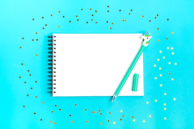 Pen in shape of unicorn, sparkles in the shape of stars and notebook on blue