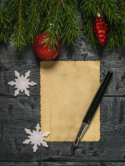 A pen and a sheet of old paper on a wooden table with spruce branches.