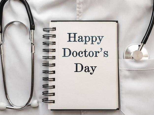 펜, 청진 기, 얼굴 마스크 및 의료 가운에 누워 눈 안경. 행복한 의사의 날. 클로즈업, 사람 없음. 친척, 친구 및 동료 축하합니다