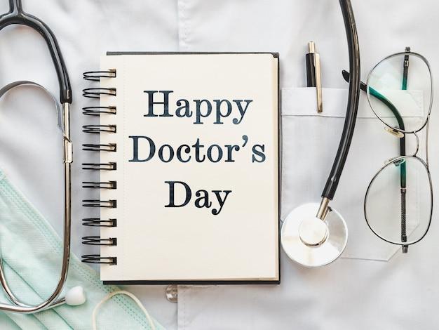 펜, 청진 기, 얼굴 마스크 및 의료 가운에 누워 눈 안경. 행복한 의사의 날. 클로즈업, 사람 없음.
