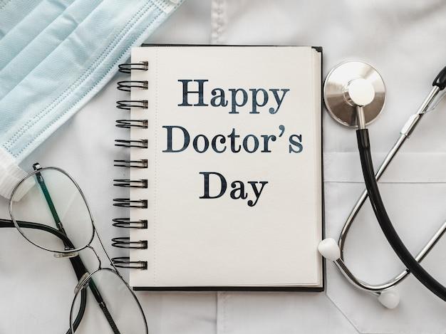 医療用ガウンの上に横たわるペン、聴診器、フェイスマスク、眼鏡
