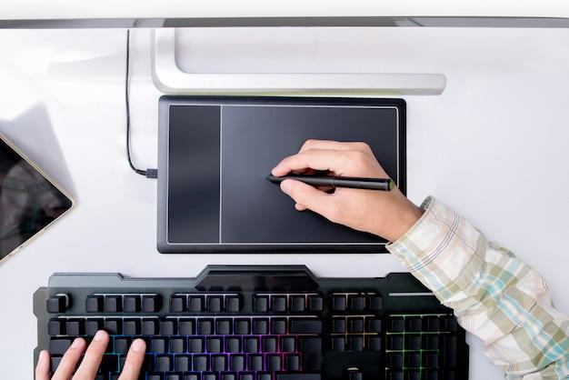 Графический дизайн работает, редактируя фото в планшете pen touch. профессиональный редактор ретуши фотографий. вид сверху.