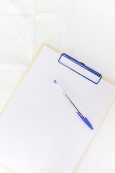 Pen over white paper on clipboard against white background