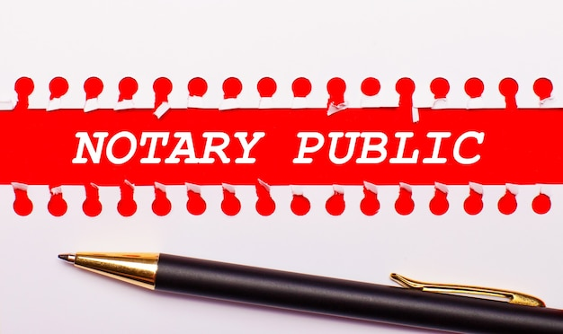 Pen and white torn paper strip on a bright red background with the text notary public