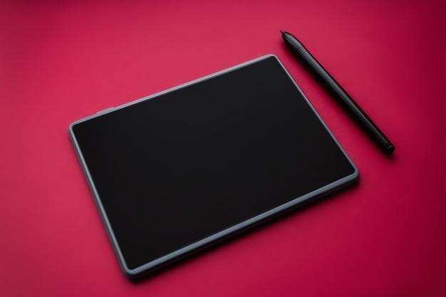 빨간색 배경에 그래픽 태블릿이 있는 펜, 클로즈업. 예술 및 작업용 가제트.