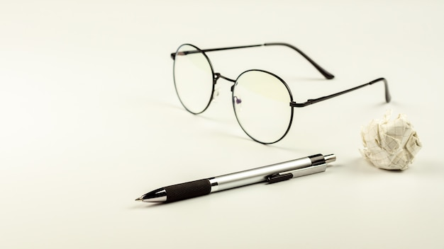 Ручка с очками и мятой бумаги мяч на белом фоне стола.
