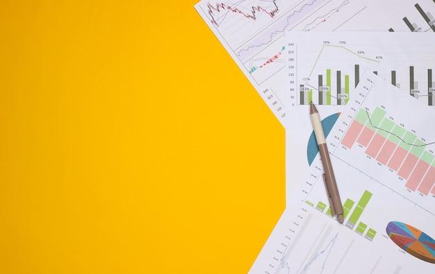 黄色の背景にグラフやチャートでペン。事業計画、財務分析、統計。上面図。コピースペース