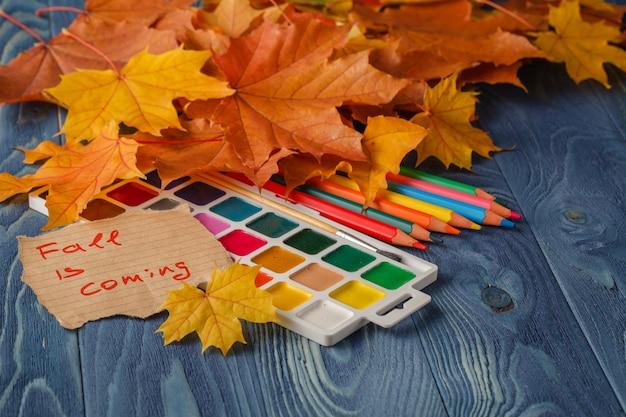 木製のテーブルに鉛筆と紅葉。学校のコンセプトに戻るレトロなスタイル。