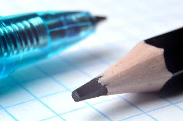 Карандаш и шариковая ручка на тетради квадратной формы. закрыть