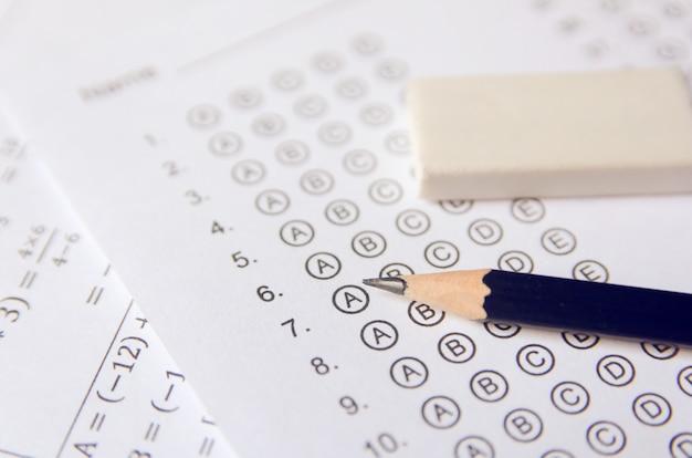 답안지에 답안이있는 표준화 된 시험 양식 또는 답안지에 연필과 지우개가 있습니다. 객관식 답안지