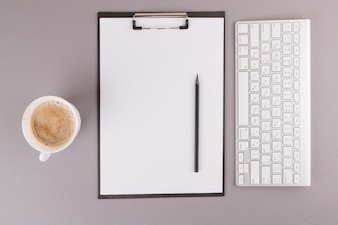 Pencil and paper on clipboard near keyboard and cup