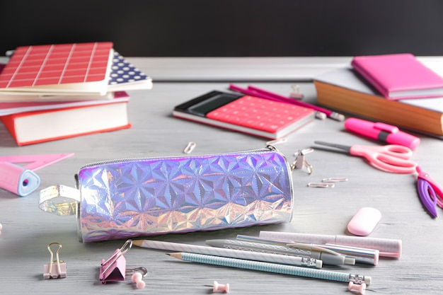 Pencil bag with stationery on desk in classroom