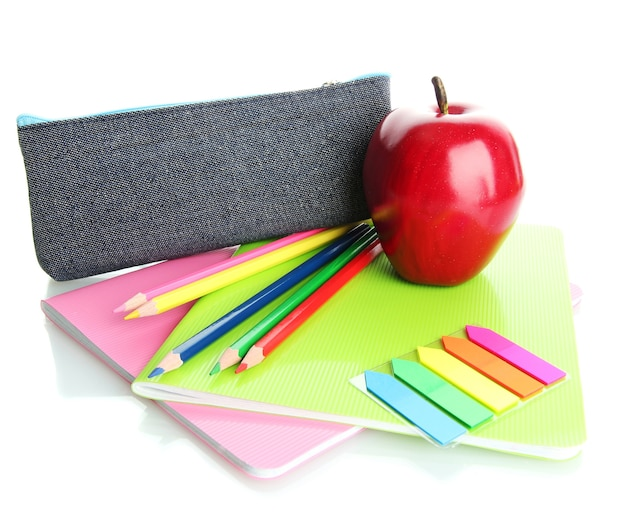 Pencil box with school equipment and apple on white