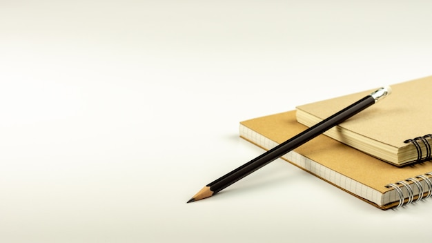 Pencil and brown diary book on white desk background.