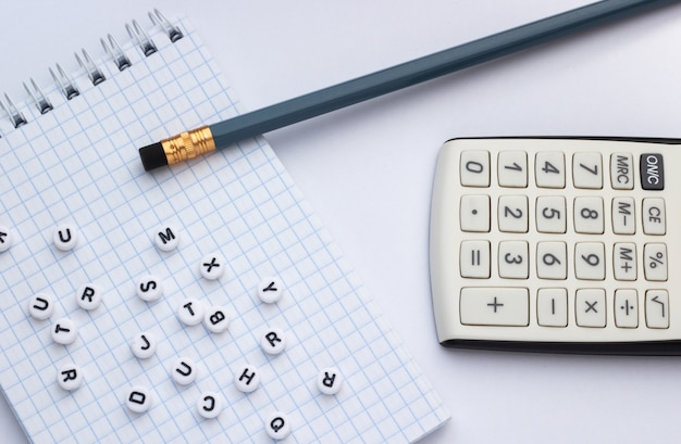 Pencil, calculator and notebook with letters on white background