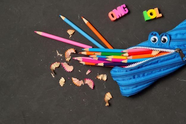 Pencil case eating pencils on black chalk