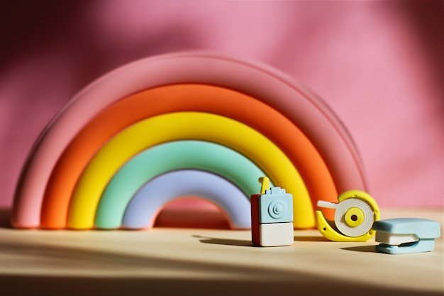 Пенал в виде яркой радуги и ластики в виде точилки, степлера и скотча на розовом фоне. концепция снова в школу, время учиться, разнообразие и инклюзивность