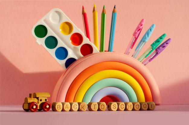 ピンクの背景に学校の科目のセットと明るい虹の形の筆箱。学校に戻るという碑文のある立方体の木製列車。