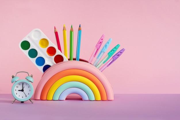 Пенал в виде яркой радуги с красками, карандаши и линейка и будильник на розовом фоне