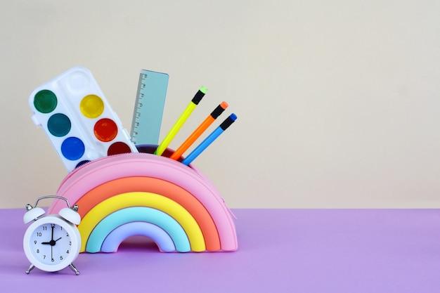 Пенал в виде яркой радуги с красками, карандаши и линейка и будильник на желто-сиреневом фоне