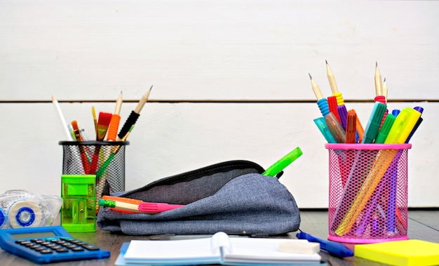 Pencil-case and school supplies on a wooden table