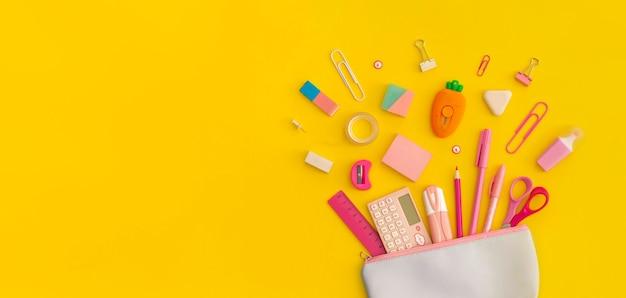 黄色の背景に学校の文房具が付いた筆箱。上面図。フラットレイ。学校のコンセプトに戻ります。