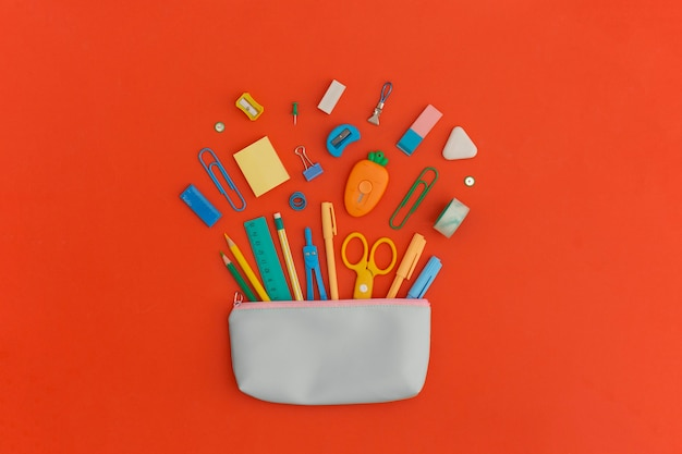 Pencil case with school stationery on a red background. top view. flat lay. back to school concept.