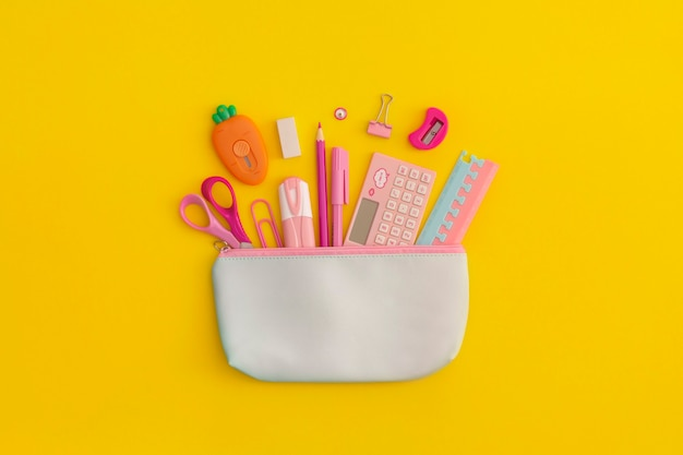 Pencil case with school stationery on a yellow background